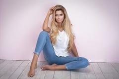 Mulher loura que levanta nas calças de brim Imagens de Stock