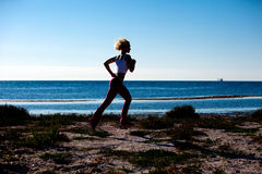 Mulher loura que movimenta-se na praia Imagens de Stock Royalty Free