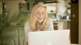 Mulher loura que olha seu portátil que ri e que giggling filme