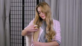 Mulher loura que penteia seu cabelo na frente do espelho com escova de cabelo video estoque