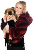 Mulher loura que prende um filhote de cachorro do pekinese Fotos de Stock