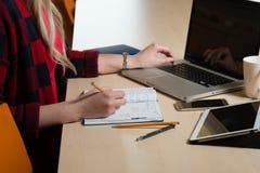 Mulher loura que senta-se em um portátil e em uma escrita Há um portátil, Imagens de Stock Royalty Free