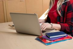 Mulher loura que senta-se em um portátil e em uma escrita Há um portátil, Imagem de Stock