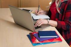 Mulher loura que senta-se em um portátil e em uma escrita Há um portátil, Fotos de Stock Royalty Free