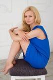 Mulher loura que senta-se em uma cadeira no vestido azul Foto de Stock Royalty Free