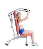Mulher loura que senta-se no exercitador Imagens de Stock