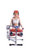 Mulher loura que senta-se no exercitador hidráulico alaranjado Imagens de Stock