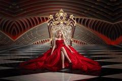 Mulher loura que senta-se no trono fotografia de stock
