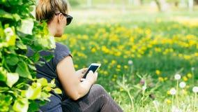 Mulher loura que texting no campo das flores pela árvore Fotos de Stock Royalty Free