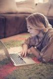Mulher loura que usa seu portátil em casa imagens de stock
