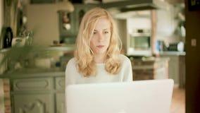 Mulher loura séria que datilografa em seu portátil filme