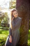 A mulher loura sensual veste o vestido cinzento, com cabelo no levantamento do vento Fotografia de Stock Royalty Free