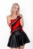 Mulher loura 'sexy' bonita com grandes peitos em um espartilho vermelho e em uma saia preta curto Imagens de Stock Royalty Free