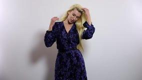 Mulher loura 'sexy' bonita na obscuridade - pose longa azul do vestido contra o fundo do estúdio Metragem do movimento lento vídeos de arquivo