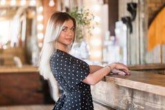 Mulher loura 'sexy' bonita que olha a câmera com sorriso, clientes de espera imagem de stock royalty free