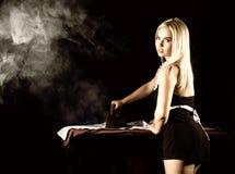 Mulher loura 'sexy' no terno da empregada, camisa branca passando com ferro velho estilo retro em um fundo escuro Imagem de Stock Royalty Free