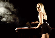Mulher loura 'sexy' no terno da empregada, camisa branca passando com ferro velho estilo retro em um fundo escuro Foto de Stock Royalty Free