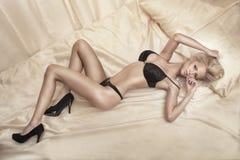 Mulher loura 'sexy' que encontra-se na cama. Foto de Stock Royalty Free