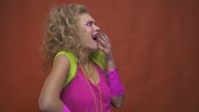 Mulher loura surpreendida do partido 80s no rosa e na roupa verde, movimento lento video estoque