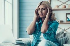 A mulher loura tem a dor de cabeça no trabalho com portátil fotografia de stock
