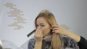 A mulher loura tinge seu cabelo Cabelo da coloração em casa video estoque