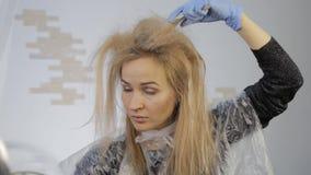 A mulher loura tinge seu cabelo Cabelo da coloração em casa vídeos de arquivo