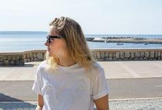 Mulher loura vestida desportiva ocasional nova com óculos de sol imagens de stock