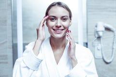 Mulher louro-de cabelo de irradiação com os pregos vermelhos que fazem a massagem de cara imagens de stock