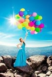 Mulher luxuosa da forma com balões à disposição na praia contra Fotografia de Stock Royalty Free