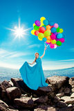 Mulher luxuosa da forma com balões à disposição na praia contra Fotos de Stock
