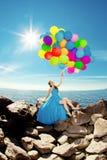 Mulher luxuosa da forma com balões à disposição na praia contra Imagem de Stock