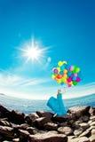 Mulher luxuosa da forma com balões à disposição na praia contra Imagem de Stock Royalty Free