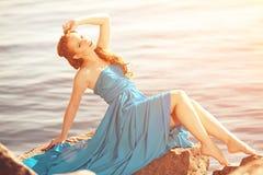 Mulher luxuosa da forma com balões à disposição na praia contra Imagens de Stock Royalty Free