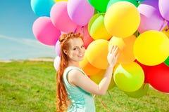 Mulher luxuosa da forma com balões à disposição no campo contra Fotos de Stock Royalty Free