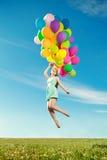 Mulher luxuosa da forma com balões à disposição no campo contra Imagem de Stock Royalty Free