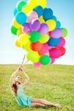 Mulher luxuosa da forma com balões à disposição no campo contra Imagem de Stock