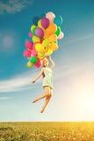Mulher luxuosa da forma com balões à disposição no campo contra Fotografia de Stock Royalty Free