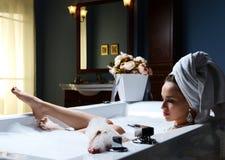 Mulher luxuosa da forma com a toalha grande macia na noite no hotel imagem de stock royalty free