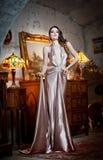 Mulher luxuoso bonita nova no vestido elegante longo. Jovem mulher bonita em um interior clássico luxuoso. Morena sedutor Foto de Stock