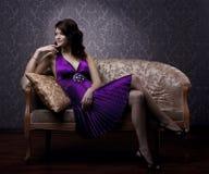 Mulher luxuoso que senta-se em um sofá do vintage do ouro Fotografia de Stock Royalty Free