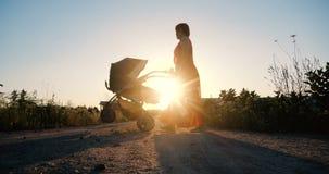 Mulher macia em um vestido vermelho que dá uma volta com seu bebê em um pram imagem de stock royalty free
