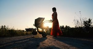 Mulher macia em um vestido vermelho que dá uma volta com seu bebê em um pram imagem de stock
