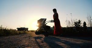 Mulher macia em um vestido vermelho que d? uma volta com seu beb? em um pram vídeos de arquivo