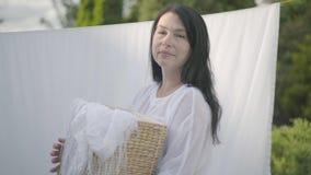 Mulher madura adorável com o cabelo preto longo que guarda a cesta de vime nas mãos ao pendurar a roupa branca em uma corda filme