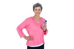 Mulher madura alegre que guarda a garrafa quando música de escuta Imagem de Stock Royalty Free