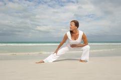 Mulher madura apta que exercita o oceano   Imagens de Stock