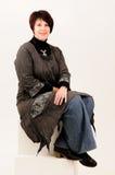 Mulher madura atrativa bonita que senta-se nas calças de brim Fotografia de Stock Royalty Free