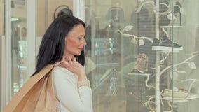 Mulher madura bonita que sorri à câmera, ao examinar a exposição de uma loja filme