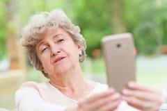 Mulher madura bonita que toma uma foto do selfie imagem de stock