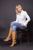 Mulher madura bonita 40s que senta-se no estúdio da cadeira Foto de Stock